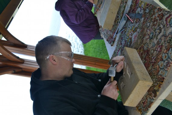 man using stone carving tools