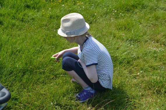 boy crouching looking at grass