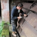 man undoing bolts on waterwheel