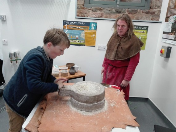 young boy hand milling on old style millstones